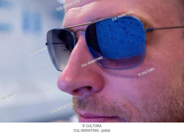 Close up of computer screen reflection in engineers sunglasses at geothermal power station