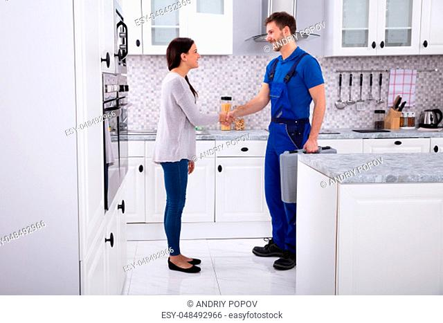 Side View Of Young Male Plumber Shaking Hands With Happy Woman