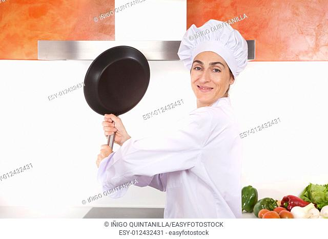 portrait of happy brunette chef woman with professional jacket and hat in white and orange kitchen ready to strike with steel blank pan
