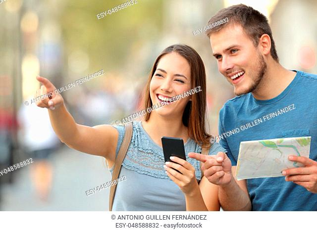 Couple of tourists checking location in a smart phone and paper map standing on the street