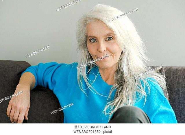 Portrait of smiling mature woman sitting on the couch at home