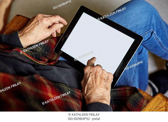 Senior woman sitting in chair, using digital tablet, elevated view