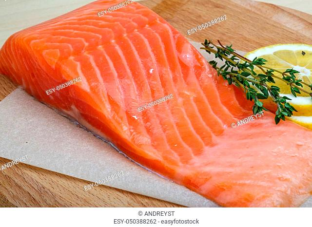 Salted Salmon on the wood background with herbs