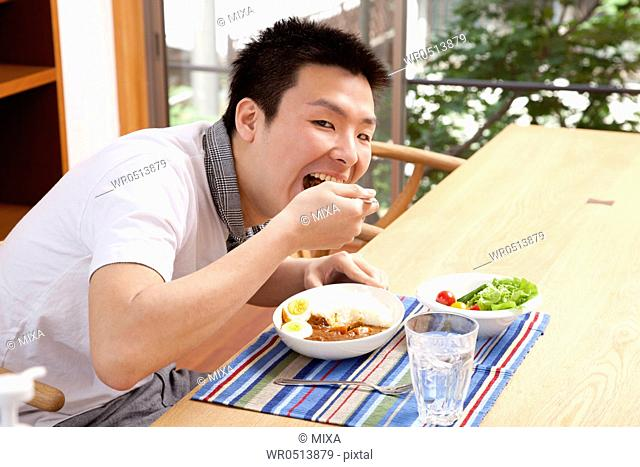 Young man eating curry and rice