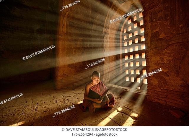 A young monk reading with rays of sunlight in the temples of Bagan, Myanmar