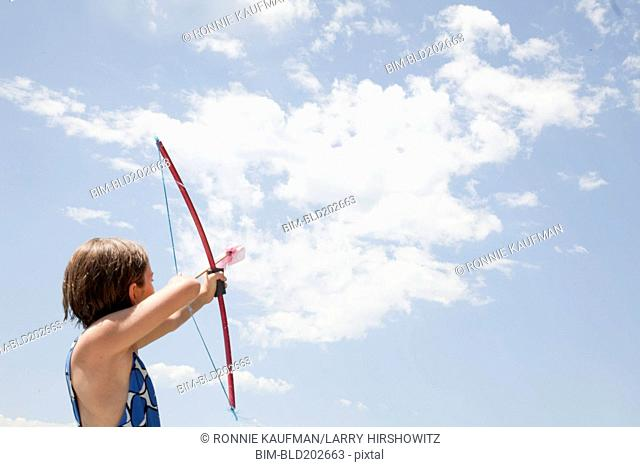 Caucasian girl aiming bow and arrow