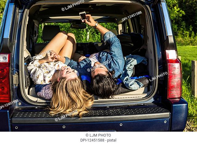 Young couple laying in the back of their packed vehicle on a road trip, showing their boots and using their cell phone; Edmonton, Alberta, Canada