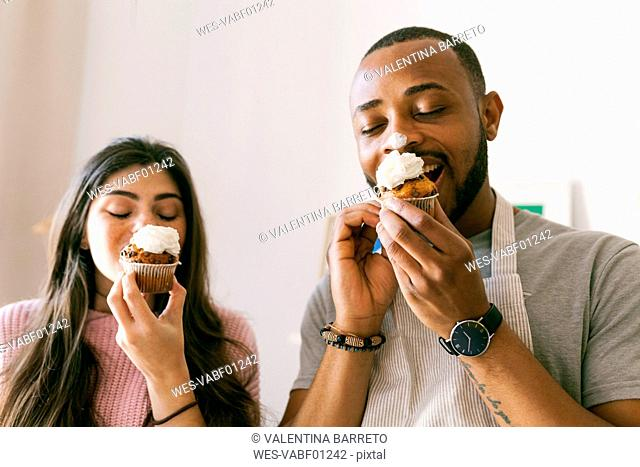 Young couple having fun, eating fresh cupcakes