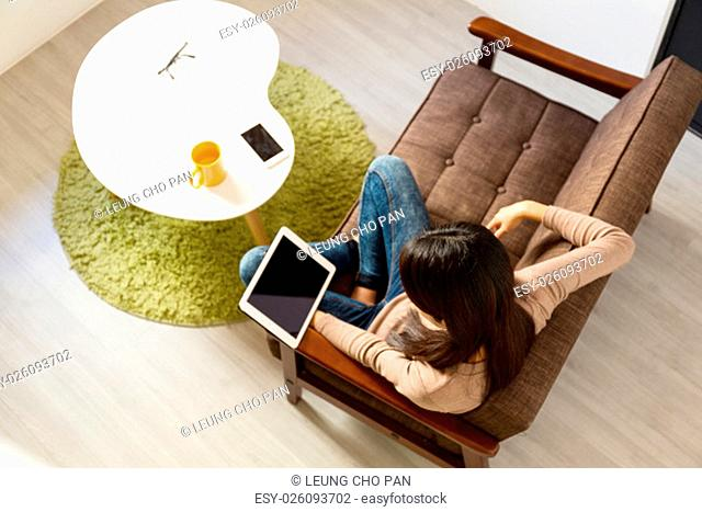 Top view of young woman reading on tablet pc at home