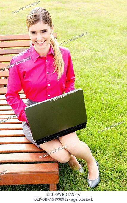 Businesswoman using a laptop in a field