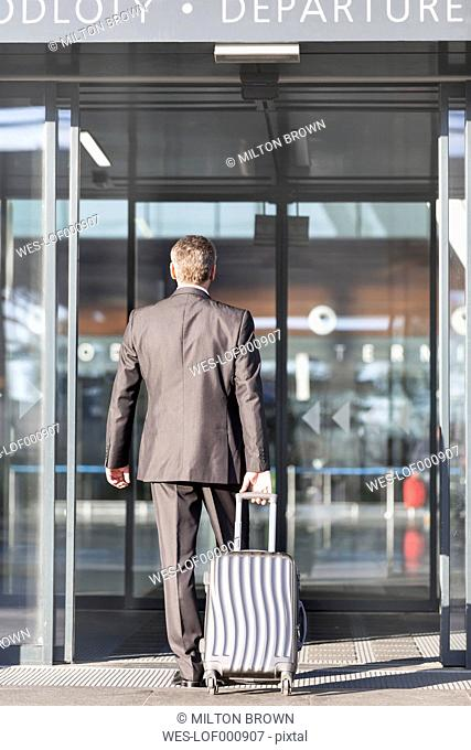 Businessman with baggage entering airport building