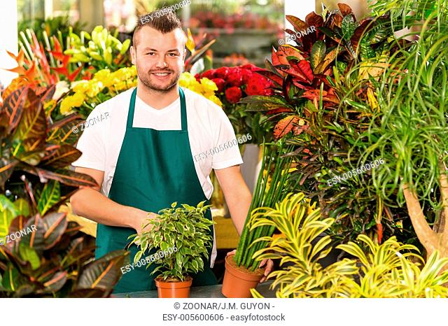 Happy male florist working flower gardening shop