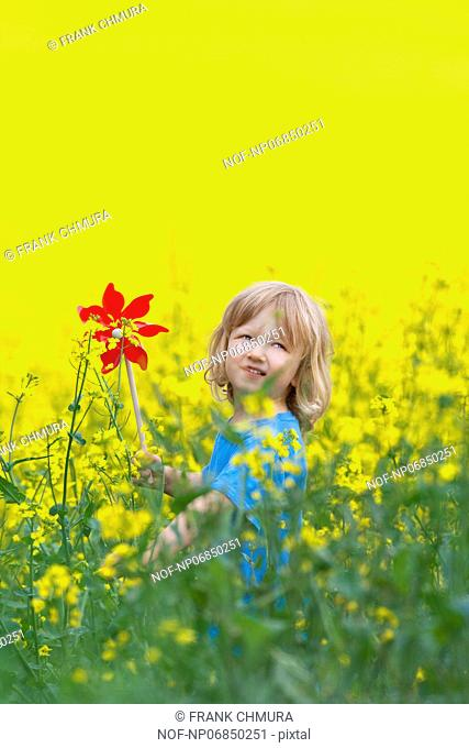 boy with long blond hair holding pinwheel in canola field