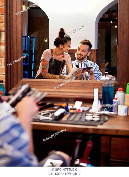 Mirror image of hairdresser showing customer magazine