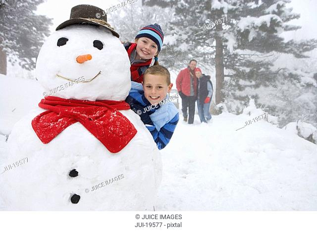 Portrait of boy and girl with snowman, parents in background