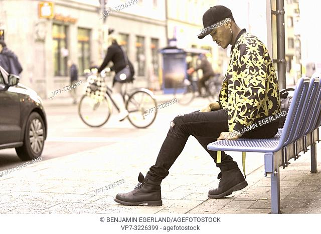 man sitting on bench at street, waiting, in Munich, Germany