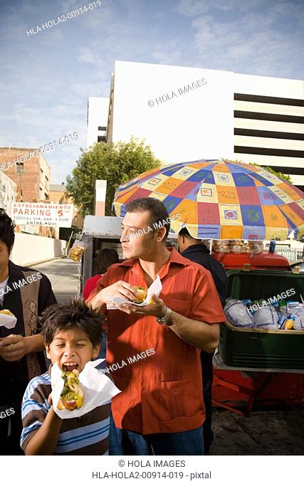 Father and sons eat hot dogs from street vendor
