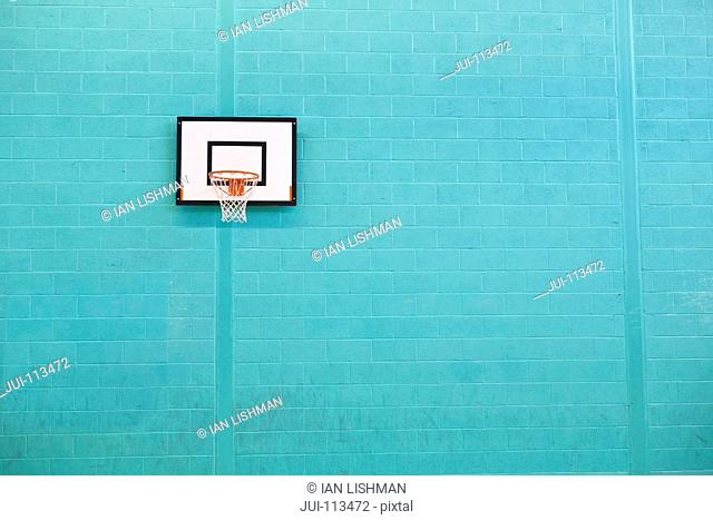 Basketball hoop hanging on turquoise brick wall in gym