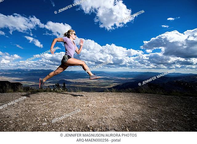 Female runner leaps in the air in front of mountain view with dramatic clouds