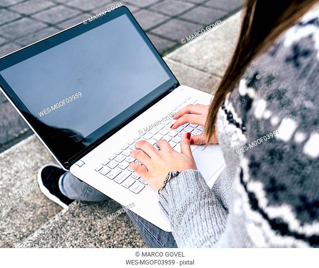 Close-up of woman sitting outdoors on stairs using laptop