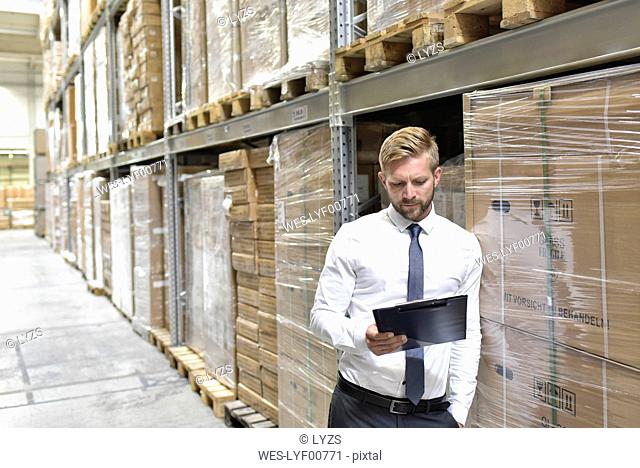 Businessman looking at clipboard in warehouse