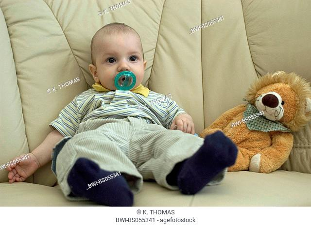 baby with smoother sitting next to a soft toy on a couch