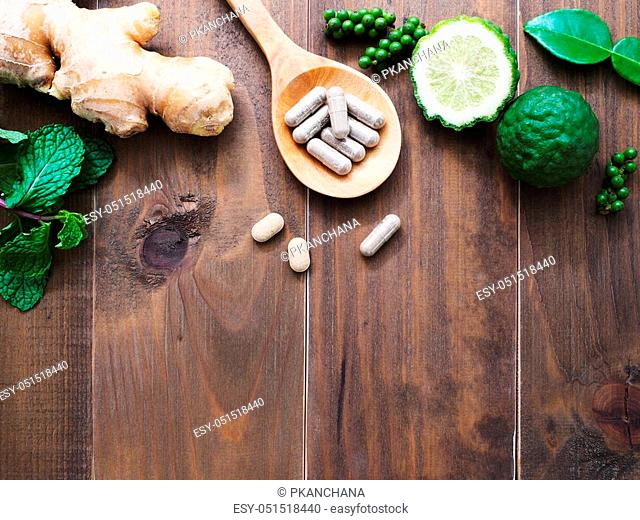 herbal pills in wooden spoon with ginger root, Kaffir lime fruit and flower on dark brown wood background with copy space. Above view