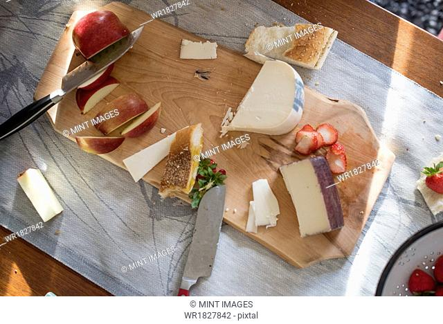Knives and a wooden chopping board with a selection of cheeses, apples and bread