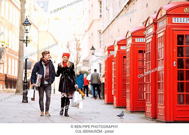 Young shopping couple strolling past red phone boxes, London, UK
