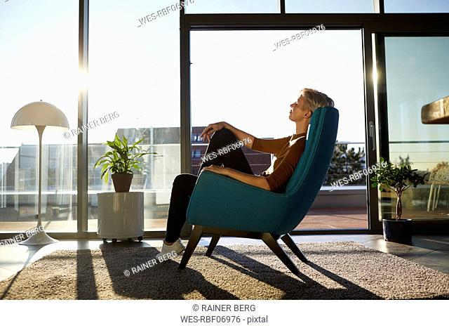 Woman sitting in armchair in sunlight with closed eyes