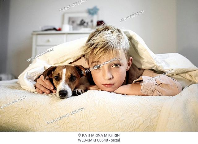 Portrait of blond boy and his Jack Russel Terrier lying together on bed