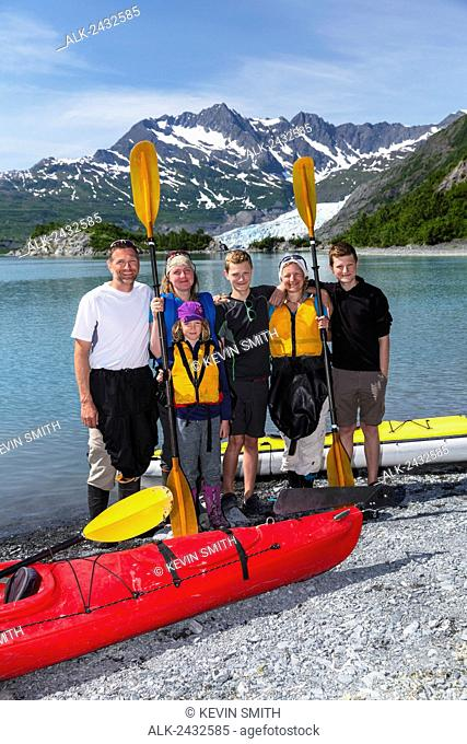 Sea Kayakers pose for a group picture on the beach with Shoup Glacier in the background, Shoup Bay State Marine Park, Prince William Sound, Southcentral Alaska