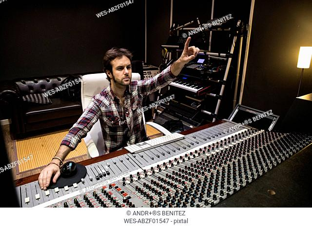 Man working in the control room of a recording studio raising his hand