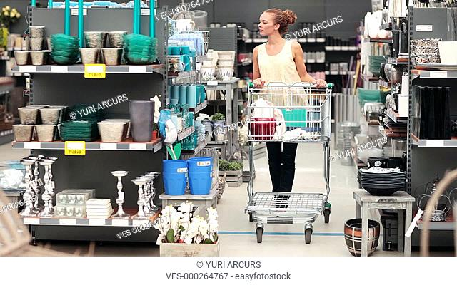 Young woman pushing her trolley through a homeware store looking at the variety of products available