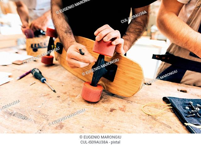 Cropped view of young men in workshop attaching wheels to skateboard