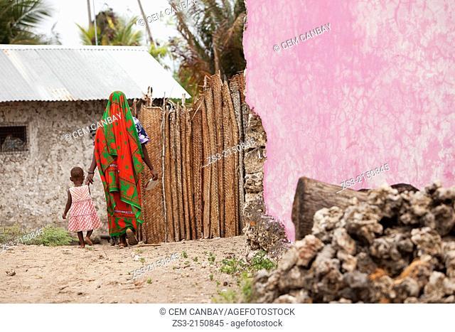 Muslim Woman in colorful dress with her child walking in the street, Jambiani village, Zanzibar Island, Tanzania, East Africa