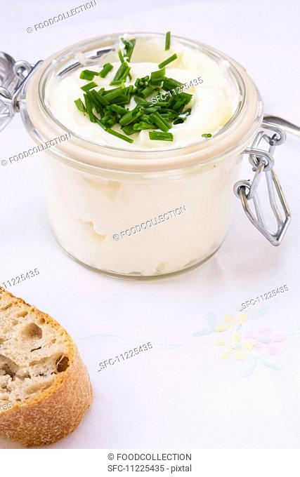 Quark with chives in a clip-top jar, and a chunk of baguette