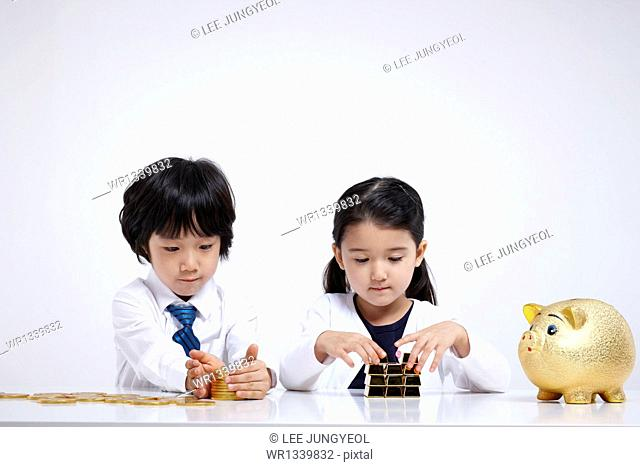 kids wearing business clothes at a table with coins and gold bars