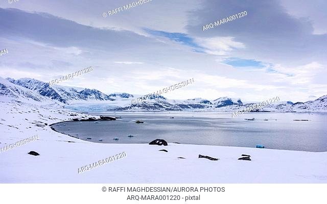 Scenic view of clouds over snowcapped coastline of Arctic Sea, Svalbard