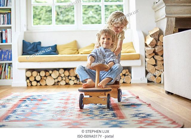 Two young brothers playing with wooden toy car