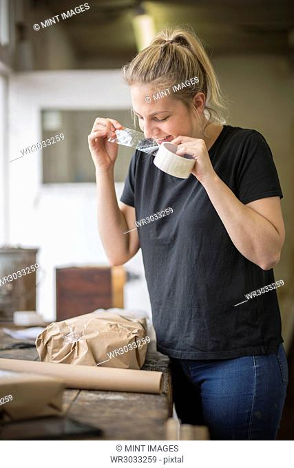 Woman standing in a workshop using her teeth on a piece of sticky tape off a roll, packets and brown packaging paper on a table
