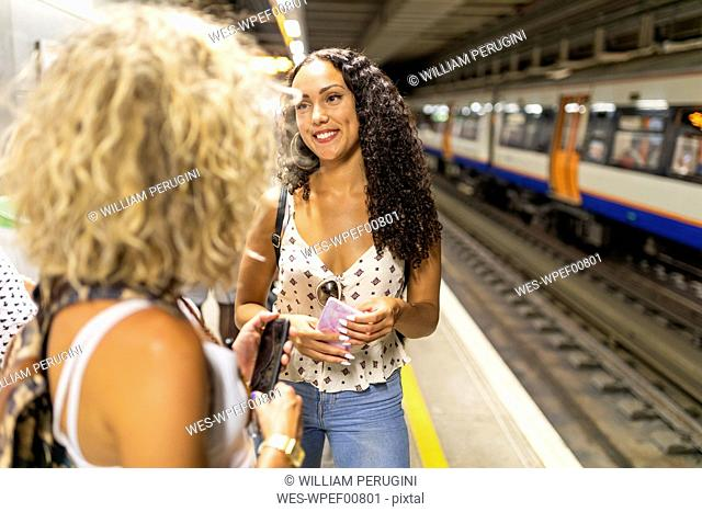 UK, London, two young women with cell phones waiting at underground station platform