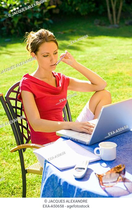 Young woman working on her notebook in the garden on sunny day