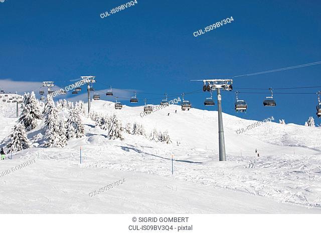 Ski resort, cable cars travelling above snowy slope, Zermatt, Valais, Switzerland