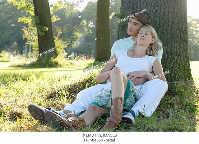 Young couple sitting underneath trea