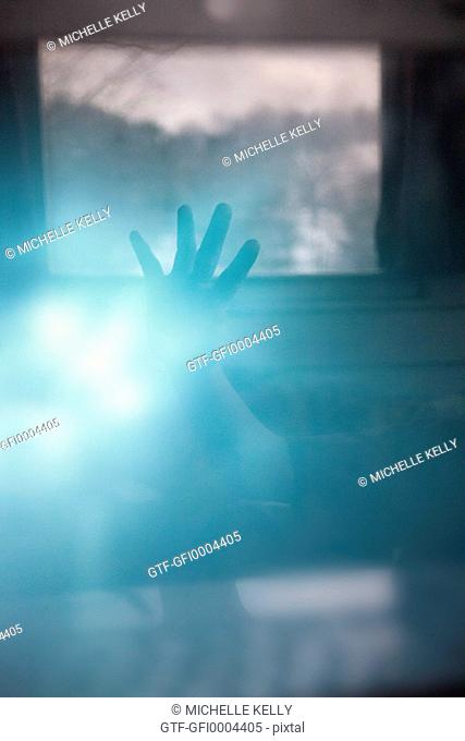 Abstract image of hand reaching toward window in blue light