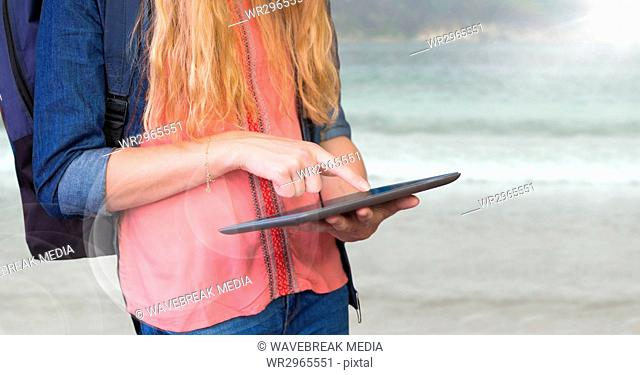 Woman mid section with backpack and tablet against blurry beach and flare