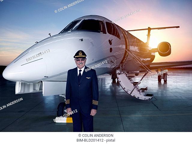 Caucasian pilot standing near jet