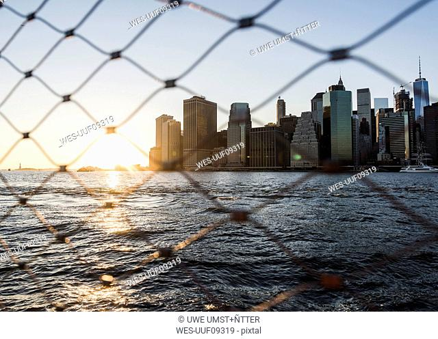 USA, Brooklyn, view to Manhattan through fence at twilight