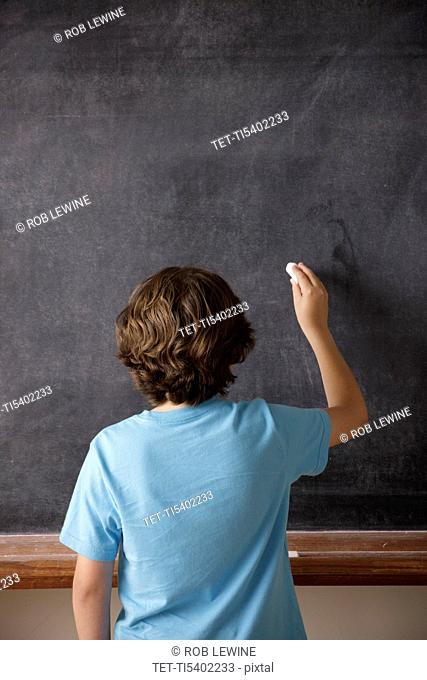 Rear view of schoolboy 10-11 writing on blackboard